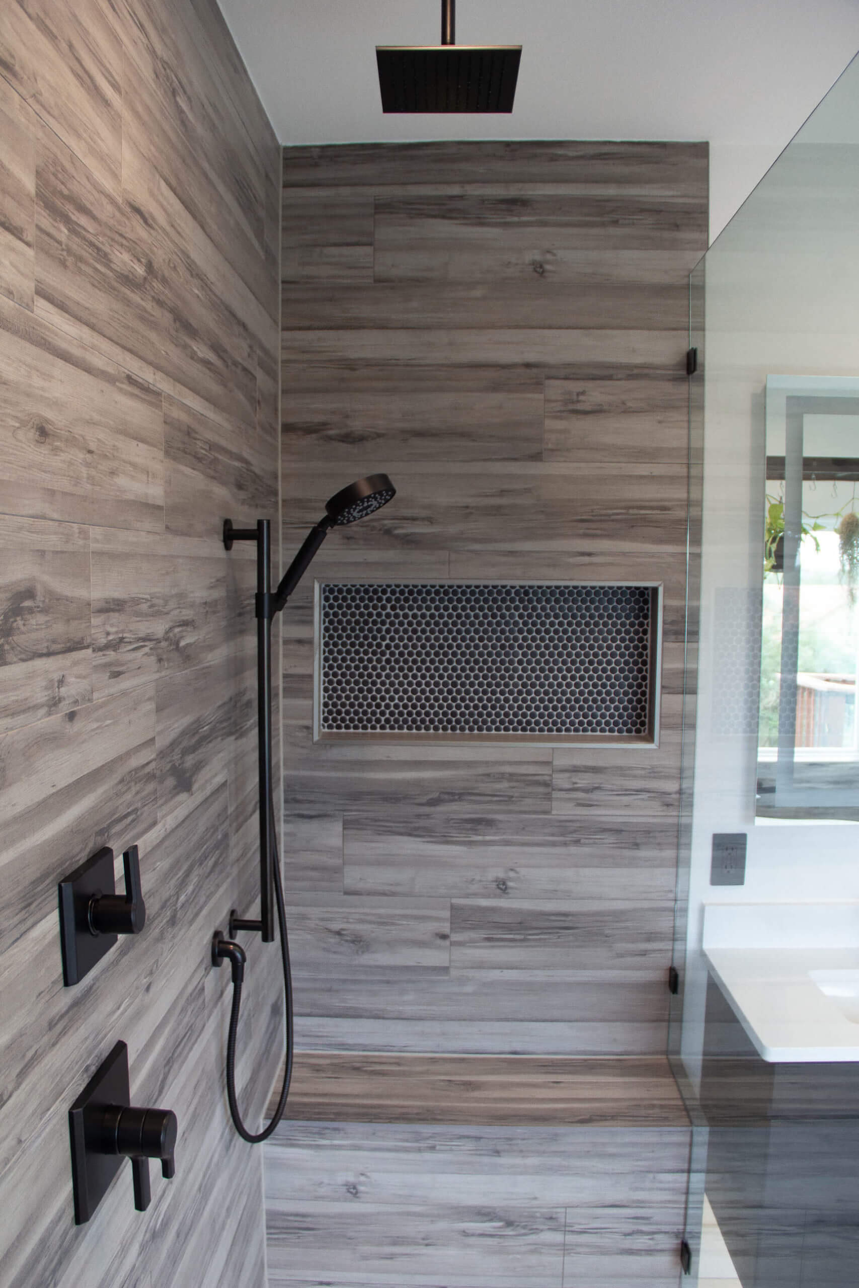 Custom shower with a wood-like interior and bronze niche