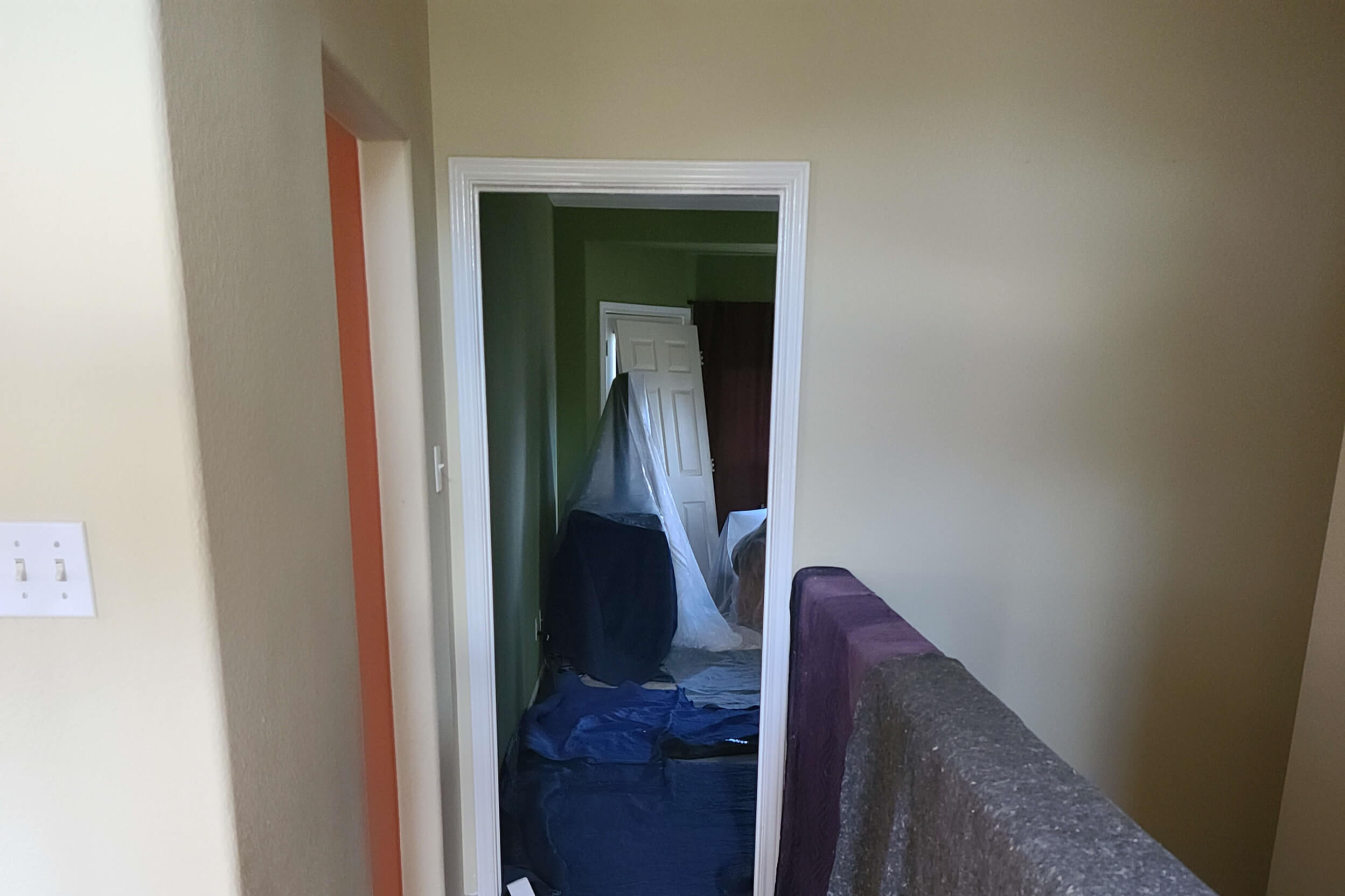 Inside of a home being remodeled with protective sheets put down on the floor and on the stair railing