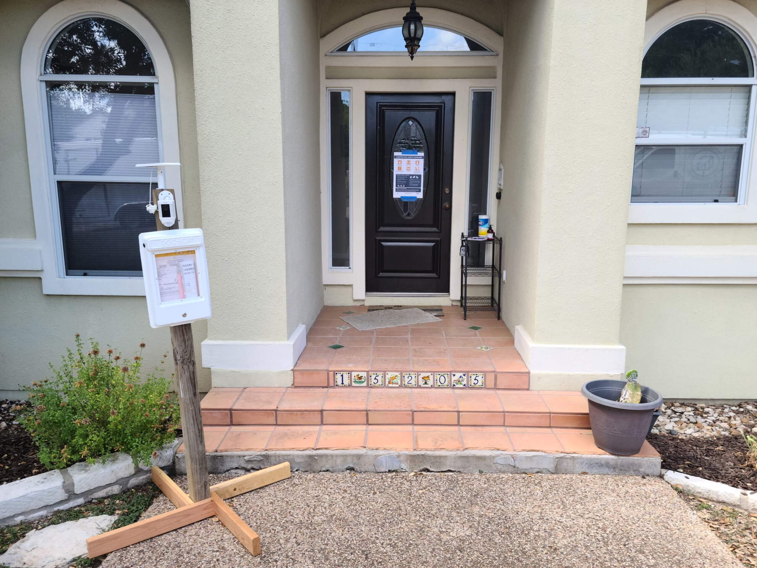 Front entrance of a home being remodeled with a sign-in sheet for safety measures