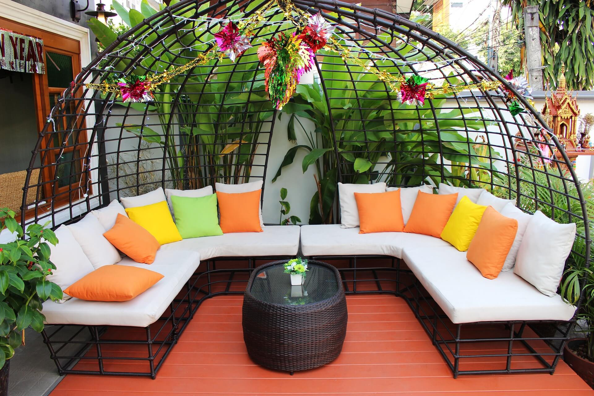 A brightly colored patio with orange flooring, and a large U shaped seating area
