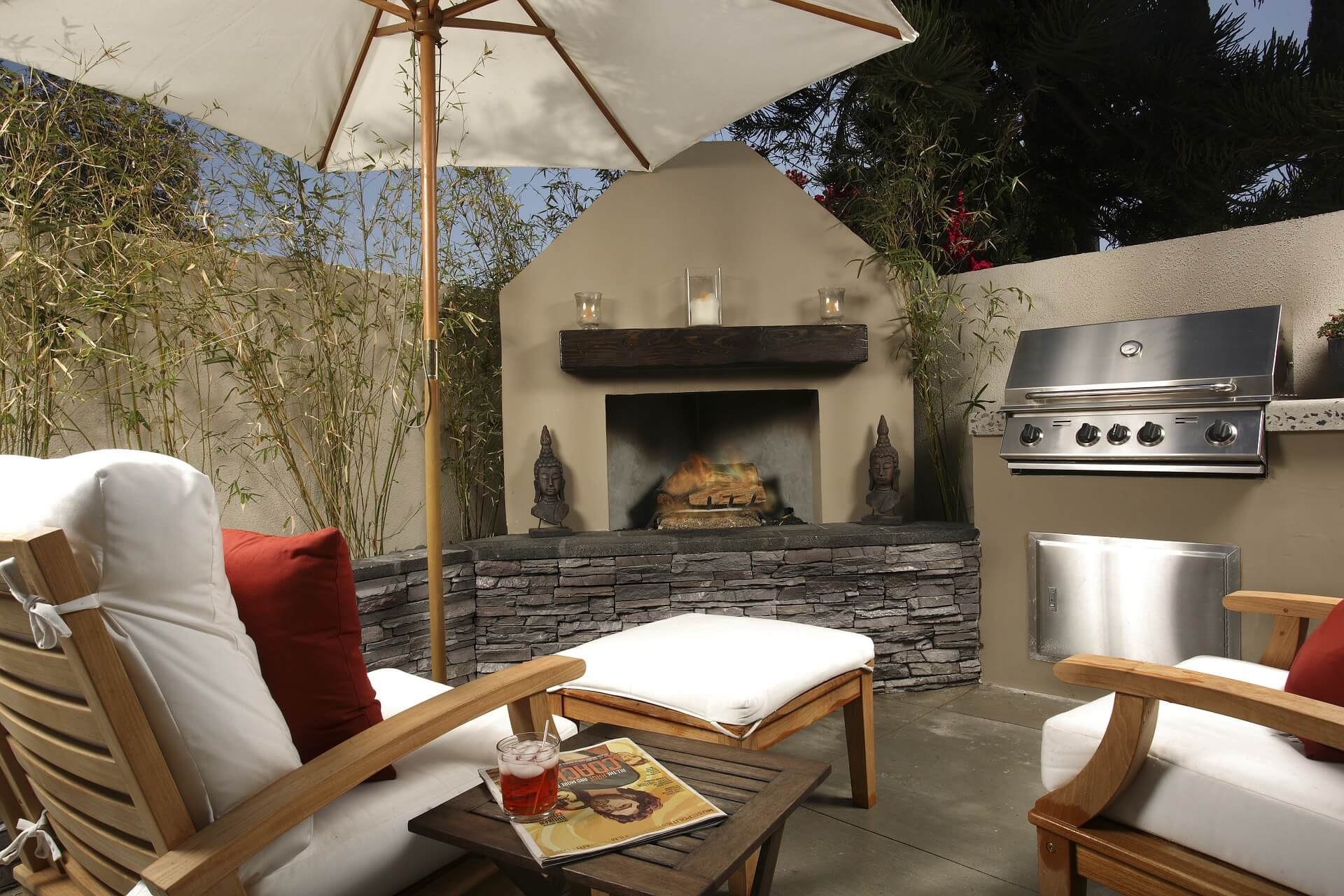 An outdoor patio area with chairs, a fireplace, and a built-in stainless steel grill