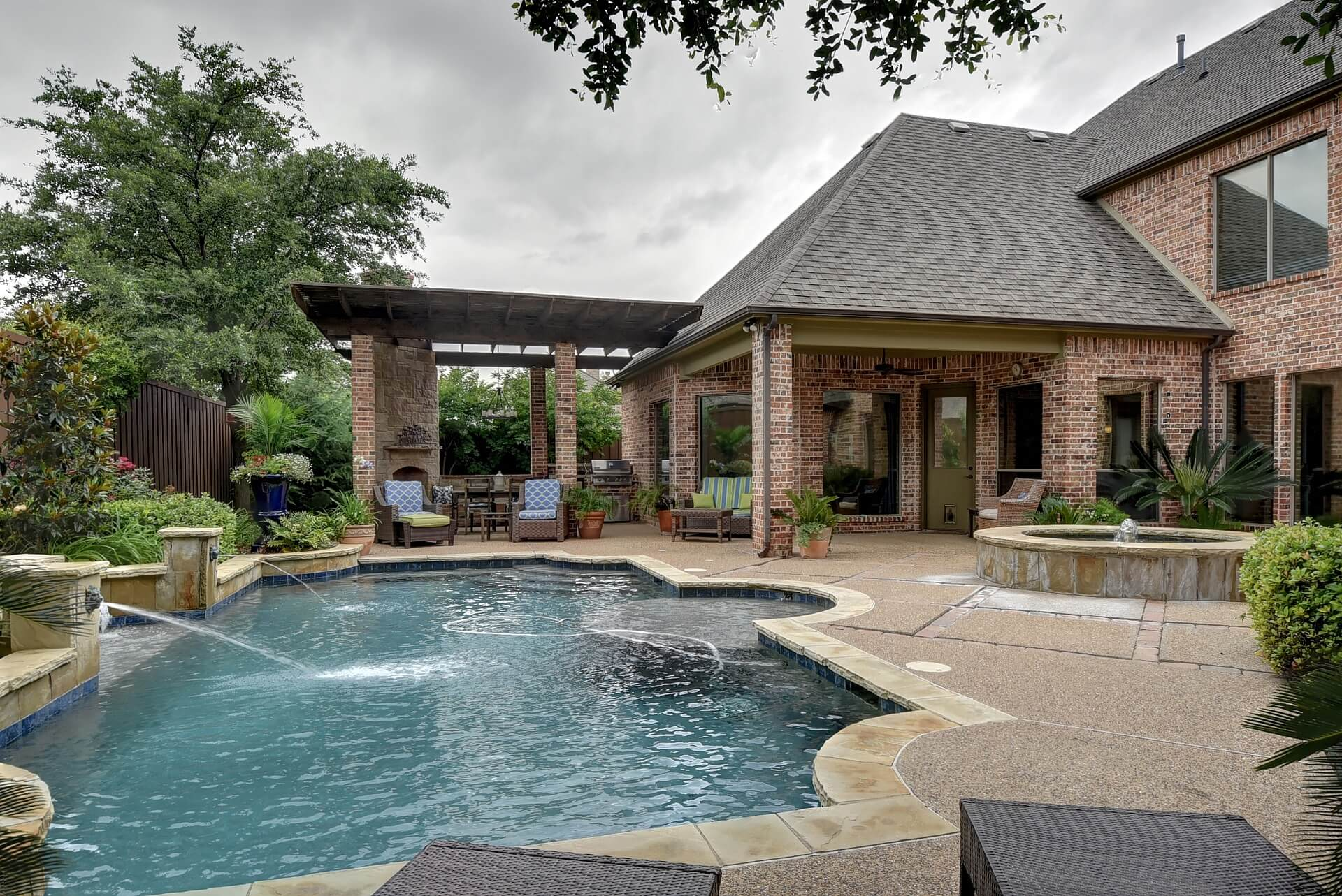 A luxurious pool with fountains next to a large brick home