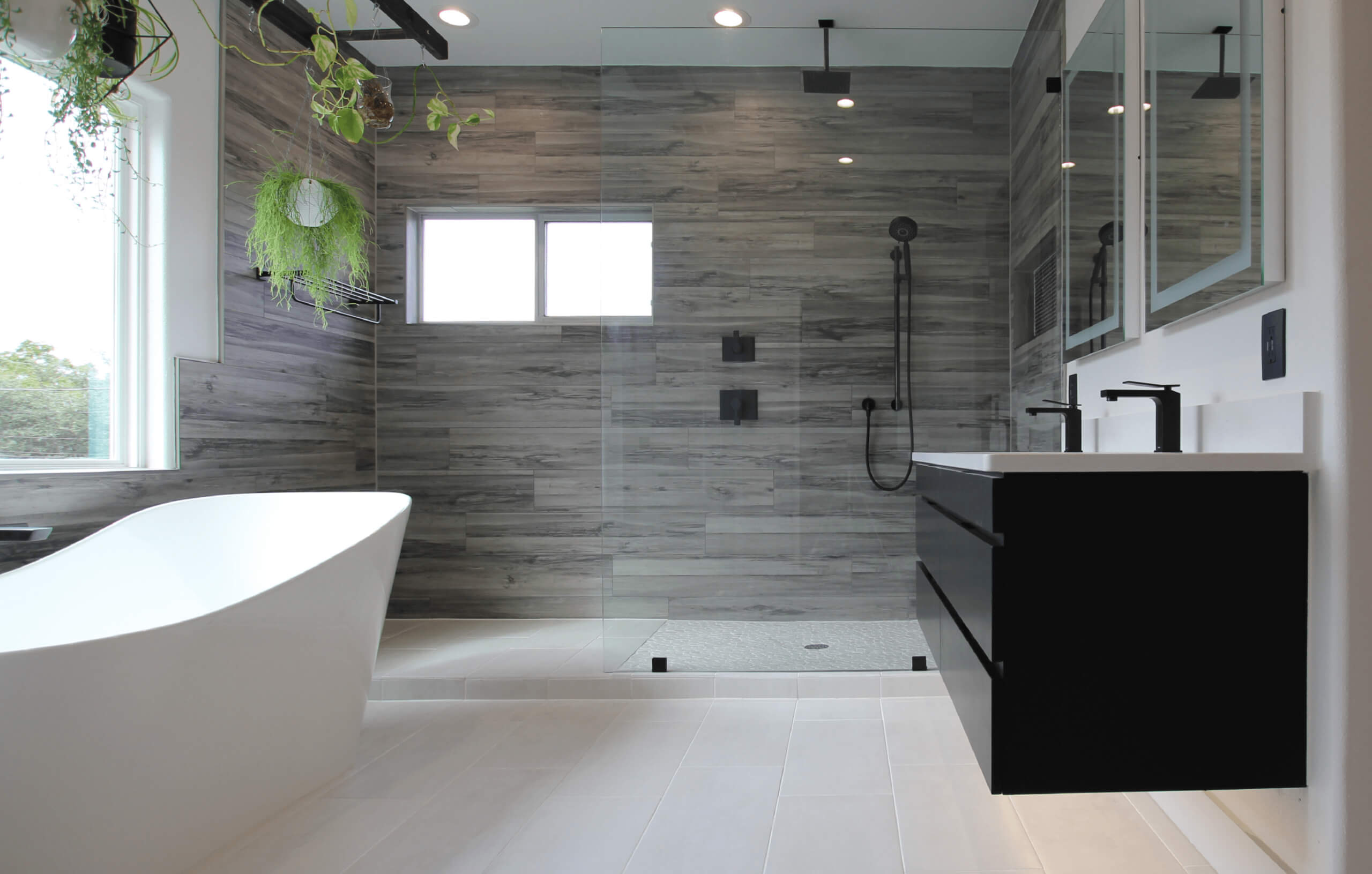 Custom bathroom with modern fixtures including free standing tub, glass shower, and floating cabinets