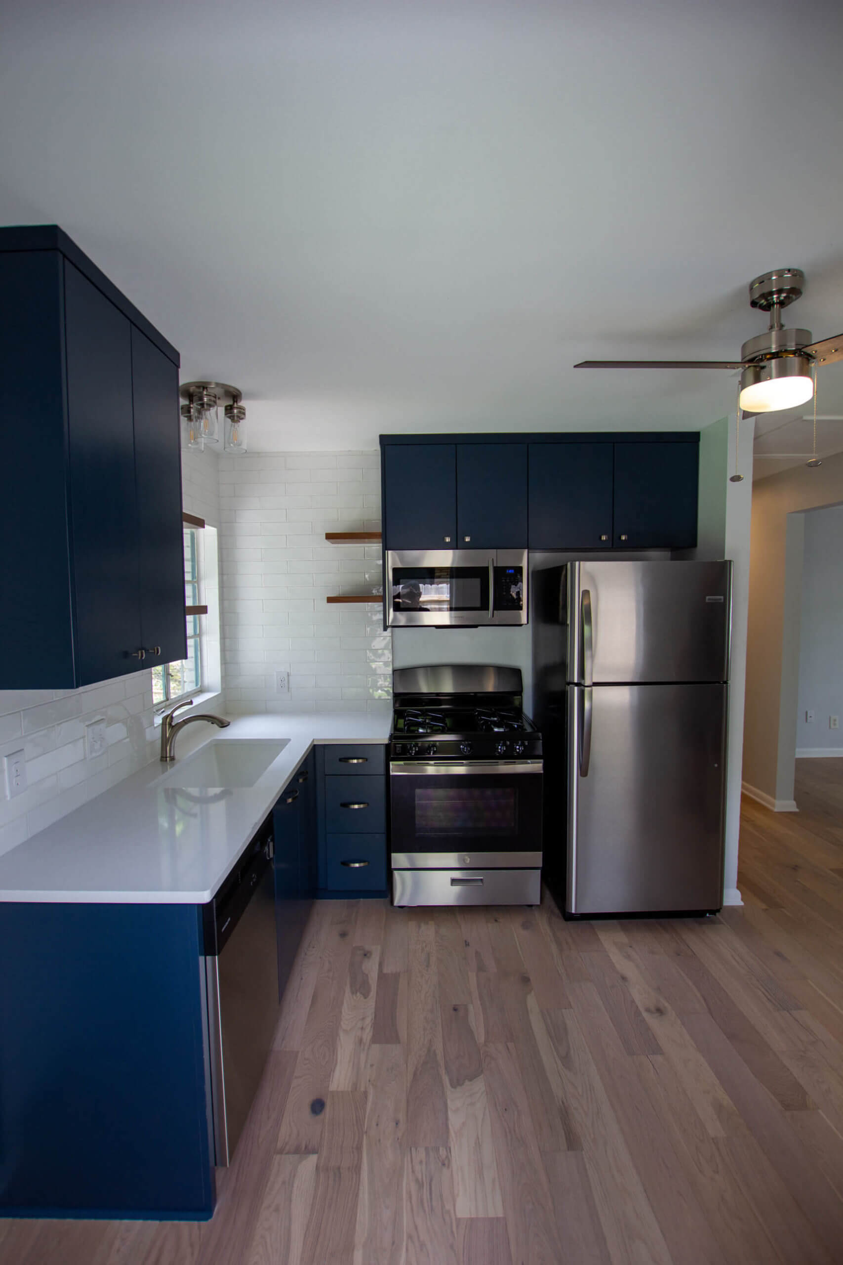 Remodeled modern kitchen with blue cabinets and stainless steel appliances.