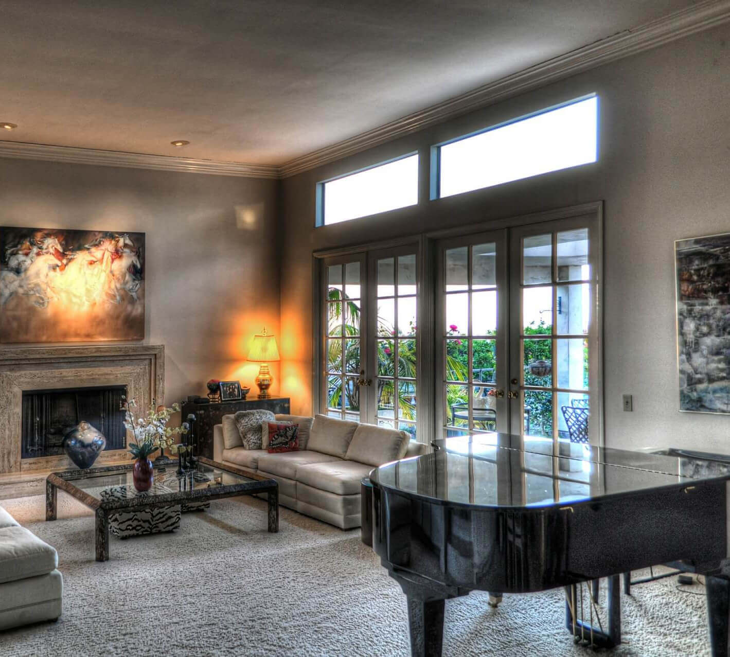 Luxurious living-room with grand piano, fireplace, and large french doors